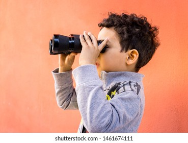 young boy is watching through field glasses