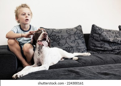 A young boy watching TV on the sofa with his big puppy.