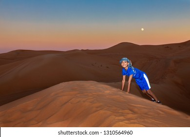 Young Boy Wearing Arabian Head Gear and Playing in the Sand Dunes of Dubai, UAE at Sunset