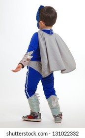 A Young Boy wearing a blue superhero suit with a gray cape, facing away from the camera