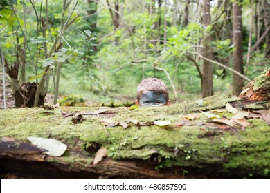 Young boy wearing camouflage face paint plays soldier while hiding among trees and logs in the forest.  Oahu, Hawaii.