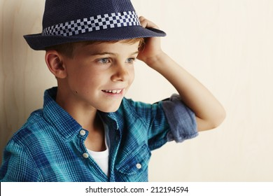 Young boy wearing checked shirt and hat