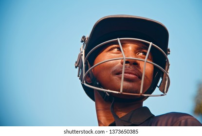 Young boy wearing a cricket helmet standing in a place