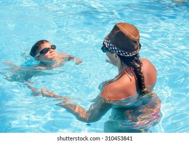 Young boy wearing goggles learning to swim with his mother in a swimming pool, view from behind the woman of his face and determined expression