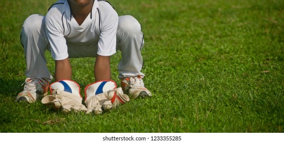 Young boy wearing hand gloves practicing wicket keeping in a field