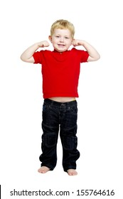 Young boy wearing jeans and a red T-shirt stood isolated on a white background looking into the camera showing his muscles