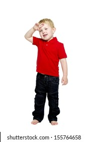 Young boy wearing jeans and a red T-shirt stood isolated on a white background wiping his brow