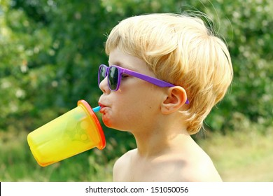 a young boy wearing purple sunglasses is tipping his head back drinking juice from a colorful sippy cup on a sunny summer day