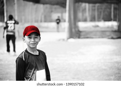 Young boy wearing red caps standing in a ground unique photo