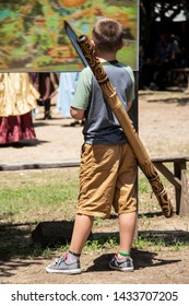 Young boy wearing shorts and tennis shoes with didgeridoo and wooden sword examines large standing map at festival or fair with blurred people in costume in distance