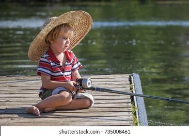 Young boy wearing a straw hat fishing
