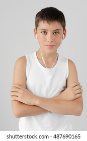 Young boy wearing white shirt and smiling on the concrete wall background