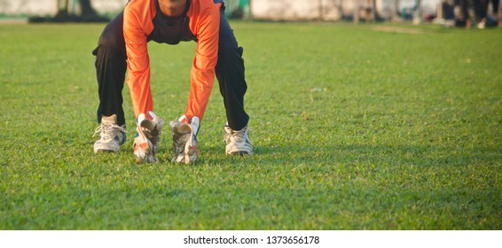 Young boy wearing wicket keeping gloves practicing in a field