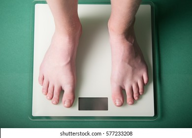 Young boy weighing himself on a bathroom scale to check his weight with a high angle view of his bare feet and a blank digital readout