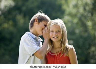 A young boy whispering to a young girl
