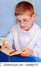 young boy in white alb going to the first holy communion and praying with prayer book