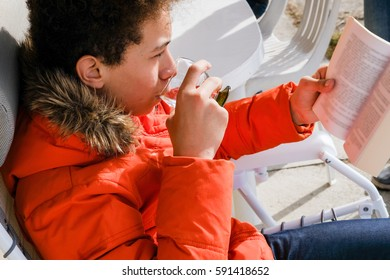 Young boy with winter clothes reading book outdoors