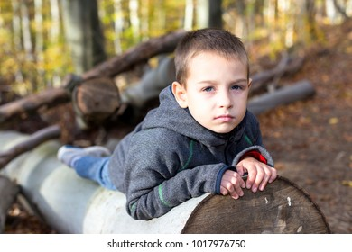 Young boy in the woods with a tree belly.