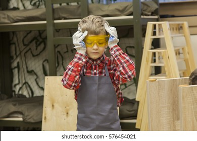 Young boy in work apron wearing protective goggles in a workshop