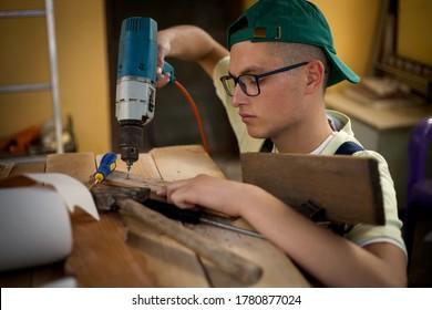 young boy works in a craft school