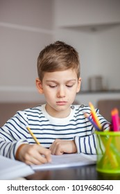 Young boy writing in his notebook looking serious