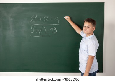 Young boy writing mathematical examples on the a school blackboard