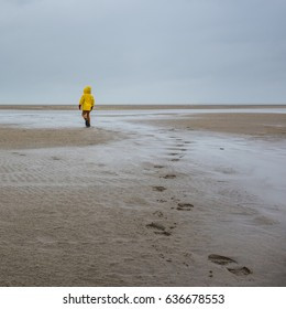 Young boy in yellow oilskin jacket walking on deserted beach in Ostend, Belgium