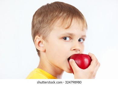 Young boy in a yellow shirt eating a ripe red apple