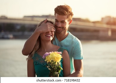 Young boyfriend is giving beautiful bouquet of flowers to his girlfriend.Man giving flowers to a woman Image is intentionally toned.