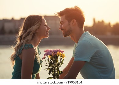 Young boyfriend is giving beautiful bouquet of flowers to his girlfriend.Man giving flowers to a woman