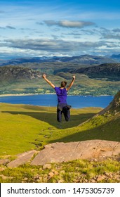 Young BoyJumps Happily On Rock In Front Of Spectacular Landscape Of Applecross Pass In Scotland