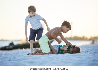 Young boys fighting on beach, older boy going to hit younger one. Siblings rivalry.