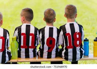 Young Boys Football Players Sitting Together on Bench. Kids Wearing Sports Soccer Striped Jerseys