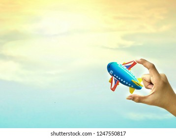 Young boy's hand holding toy airplane with summer sky background, enjoy lifestyle and air travel in child's perspective concept