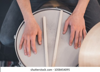 Young boy's hands holding wooden drum sticks on red vintage drums, snare, hi-hat, bass drum in the house with stripped colorful carpet