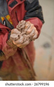 Young boy's hands squeezing clay/mud.