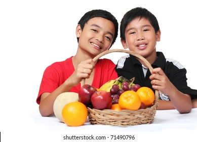 Young boys holding a basket of fruits