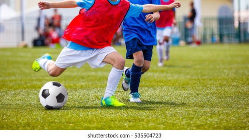 Young Boys Kicking Soccer Ball on Green Grass Pitch. Football School Tournament For Kids. Players in Red and Blue Jersey Shirts Fighting For Ball
