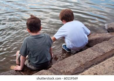 Young boys play beside lake