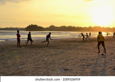 Young boys playing cricket game on a beach. Silhouettes of young anonymous boys having fun on Sri Lanka beach. Golden sunset light with sunbeams in Weligama.
