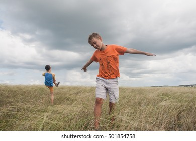 young boys playing in a field. boys running across the field with his hands in different directions. boy shows flying plane. children fun games. two boys. Boy shows a plane