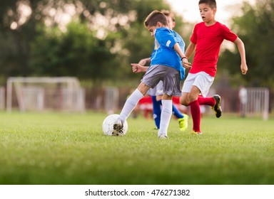 Young boys playing football soccer game on sports field
