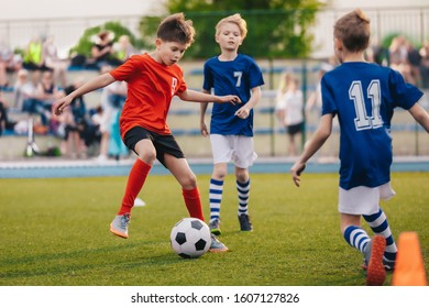 Young boys playing soccer game. Training and football match between youth soccer teams. Junior competition between players running and kicking soccer ball. Final game of football tournament for kids