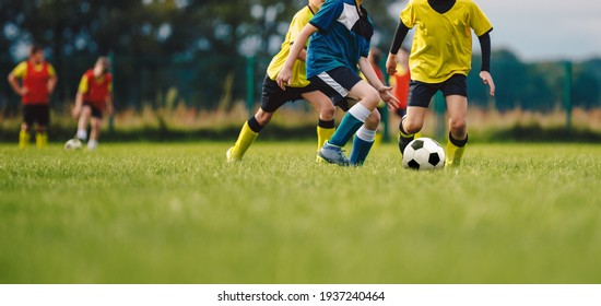 Young boys playing soccer game. Kids having fun in sport. Happy kids compete in football game. Running soccer players. Competition between players running and kicking football ball. Football school