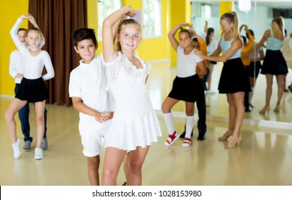 Young boys and positive girls enjoying active dance in studio