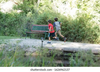 Young boys running in park near water with bench