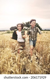 young boys  running in the wheat field