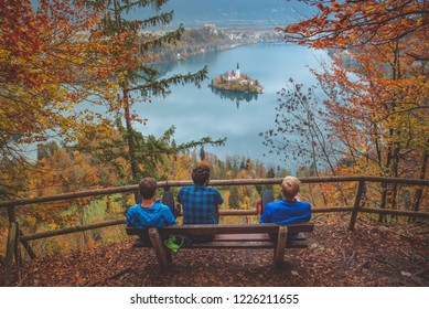 Young boys sitting on bench Bled Lake, Island,Church And Castle With Mountain Range. Slovenia, Europe
