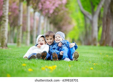 Young boys sitting on grass in park and having fun