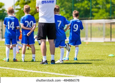 Young Boys In Soccer Football Team With Coach. Reserve Players on a Team Bench. Motivation Talk Before Soccer Match. Little League Soccer Boys Team.